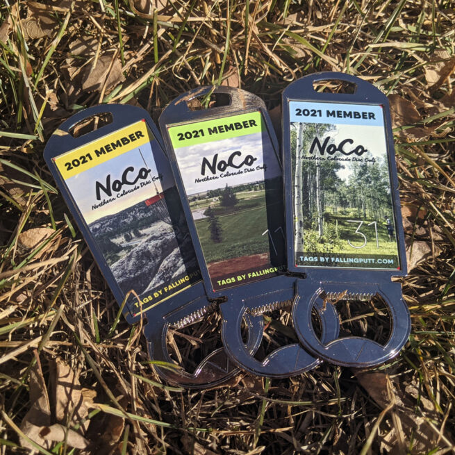 Shows three of the 2021 membership tags for Northern Colorado Disc Golf laying in some brownish grass. They are a rectangular, shiny metal bottle opener with a NoCo logo and the number for the tag overlayed on top of a photo of a different disc golf hole. Each tag has a different color of stripe across the top that says 2021 Member.